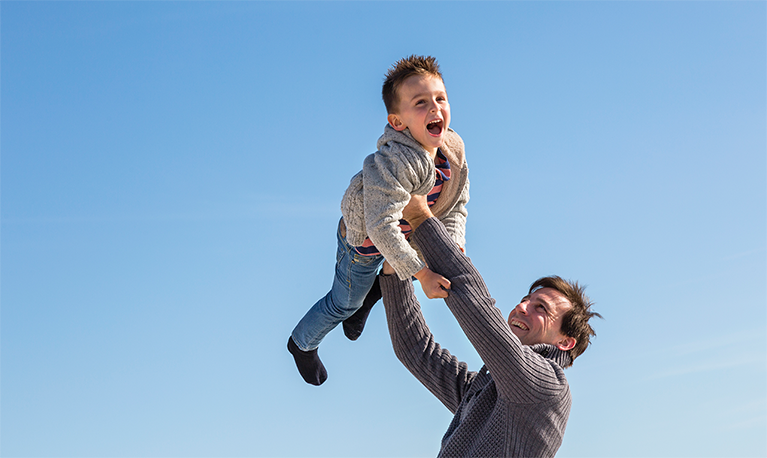 A picture of a man lifting a boy over his head and posing for a photo.
