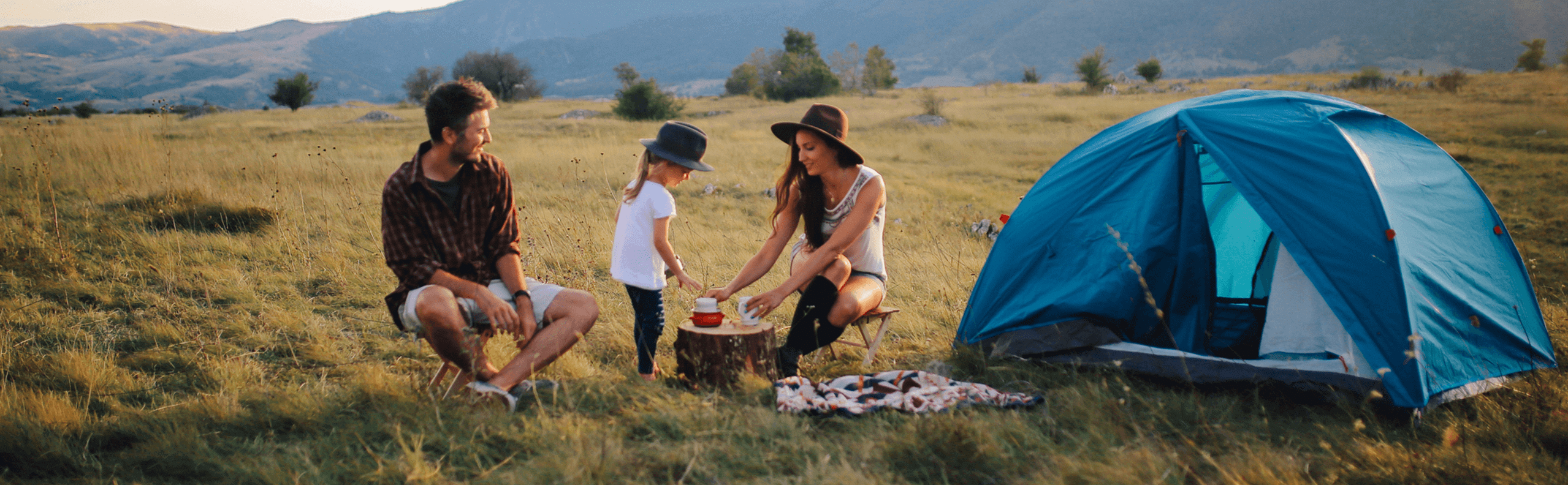 A man, woman and child camping in a field
