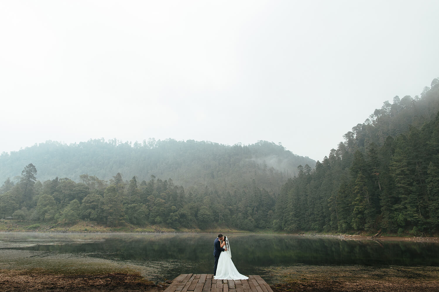 A bride and groom kissing on a dock