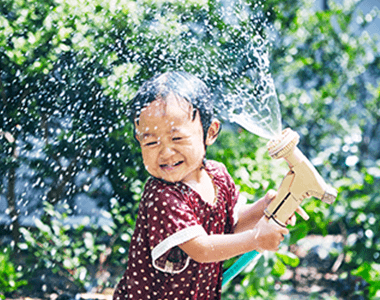 A baby playing with a water hose